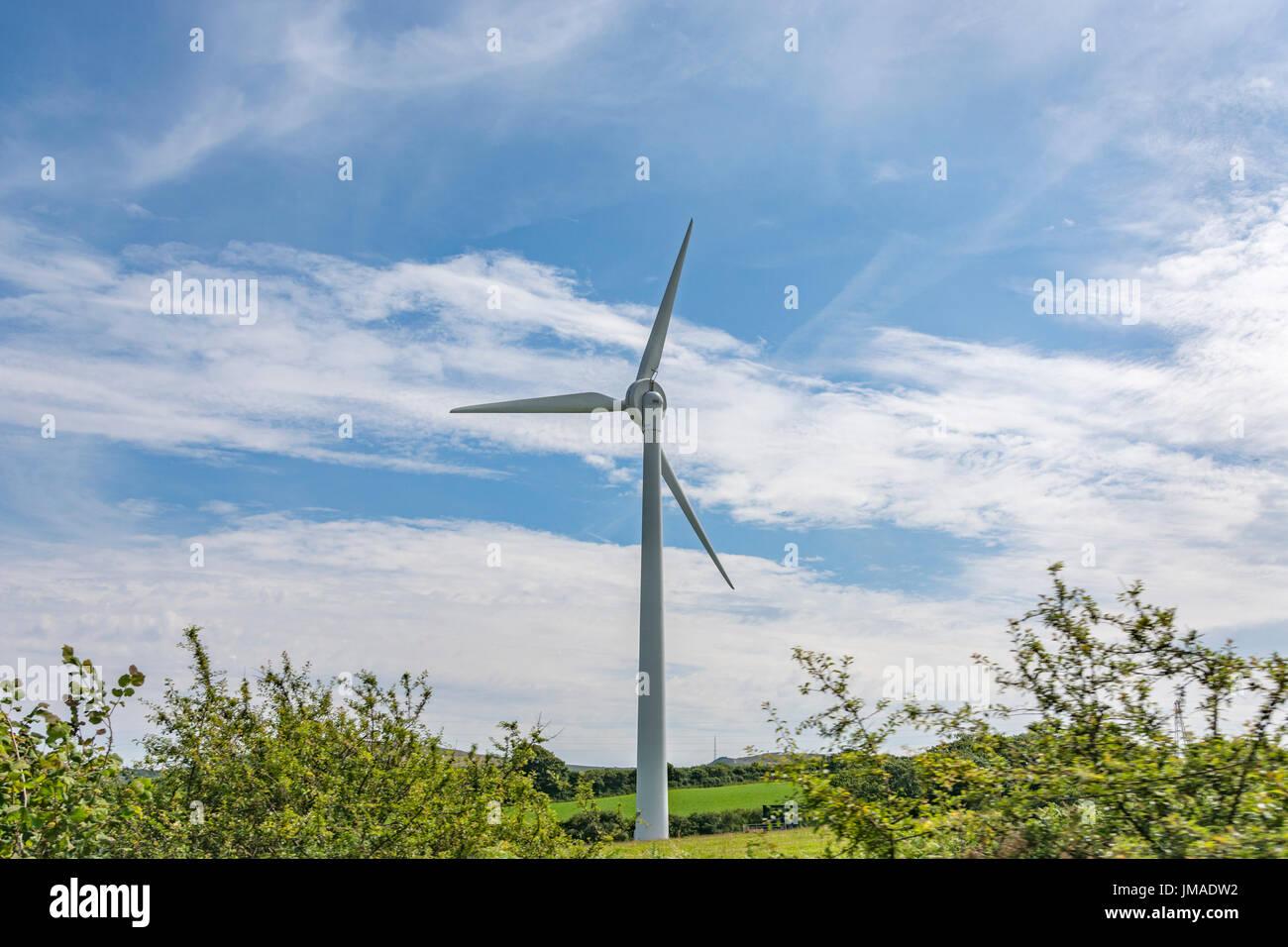 Giant wind turbine / wind generator in a field set against blue sky and sun. Metaphor clean energy, renewables, wind energy. - Stock Image