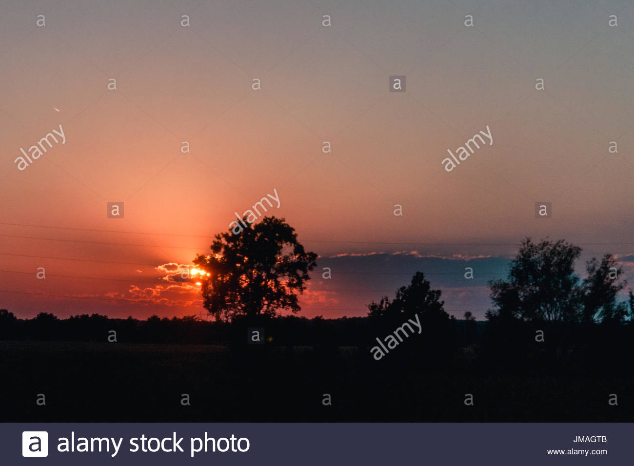 Sunset behind a cloud. - Stock Image