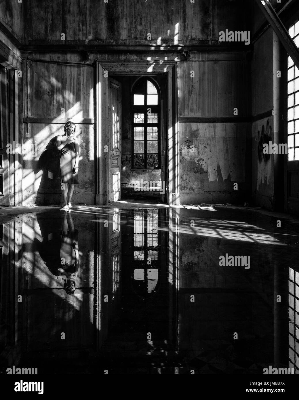 Young Woman Standing In Abandoned Building - Stock Image