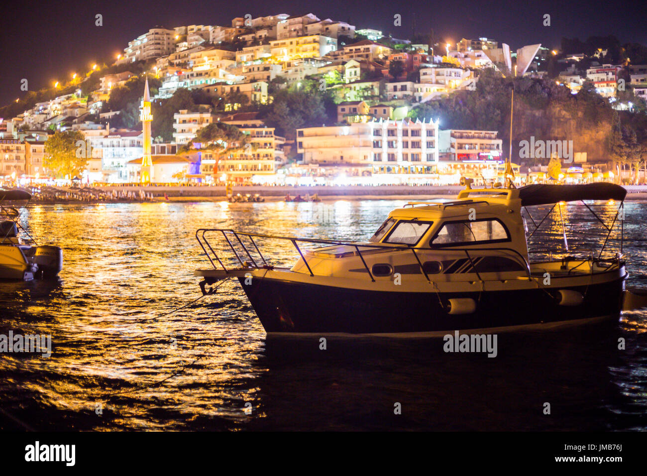Closeup of a boat on sea with city lights in the background in the evening - Stock Image