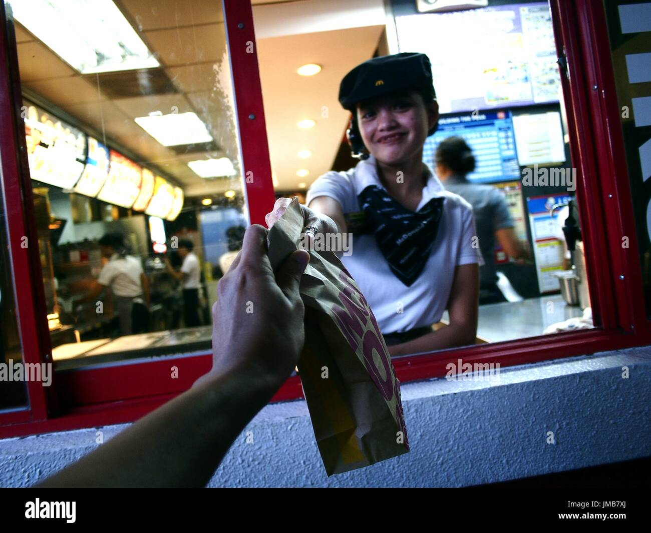 ANTIPOLO CITY, PHILIPPINES - JULY 17, 2017: A fast food chain worker gives a customer a purchased product at a drive thru. - Stock Image