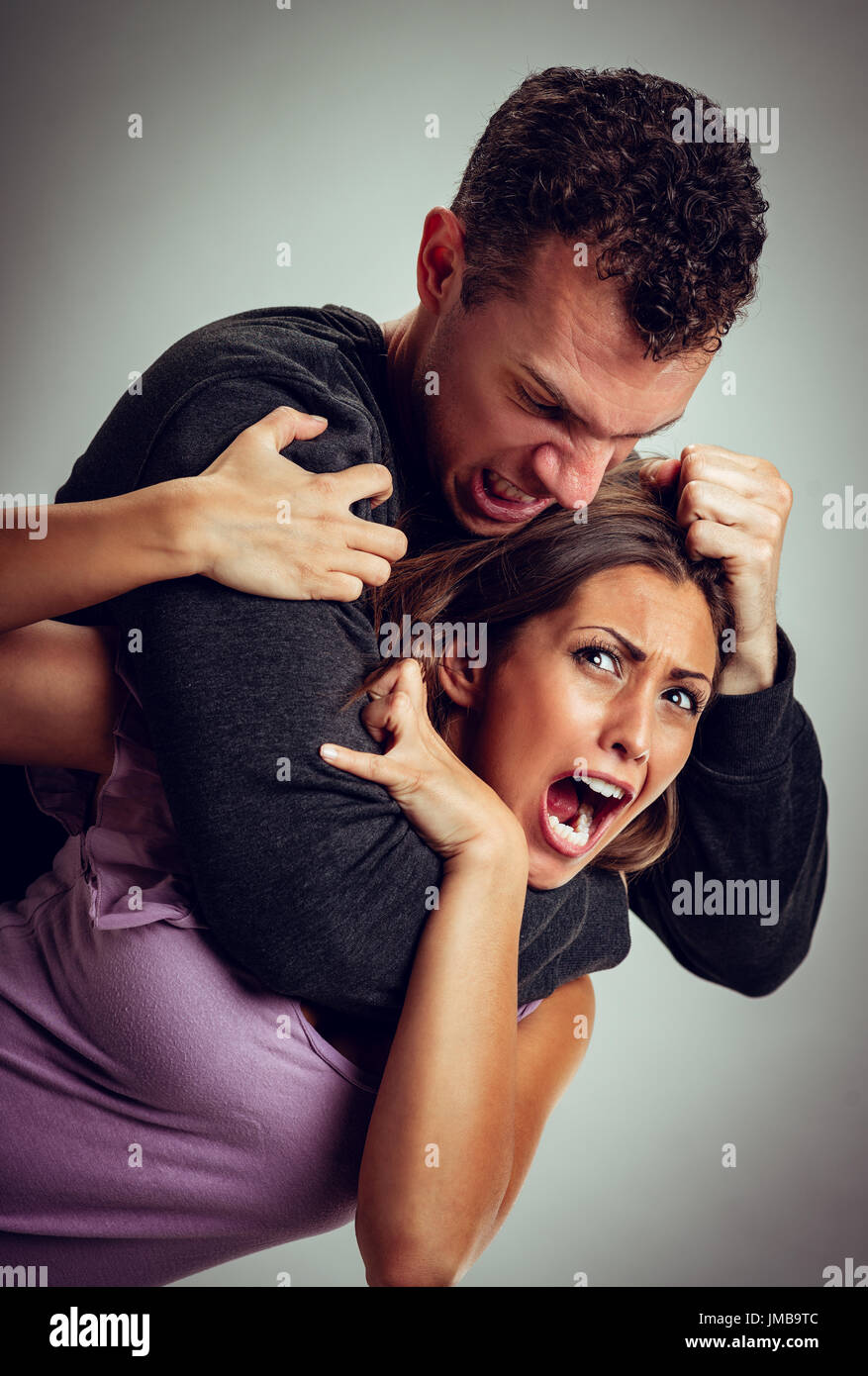 Angry aggressive husband trying to hit and choking his wife. - Stock Image