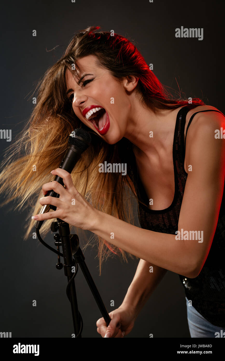 A young woman rock singer with tousled long hair holding a microphone with stand and sing with a wide open mouth. - Stock Image