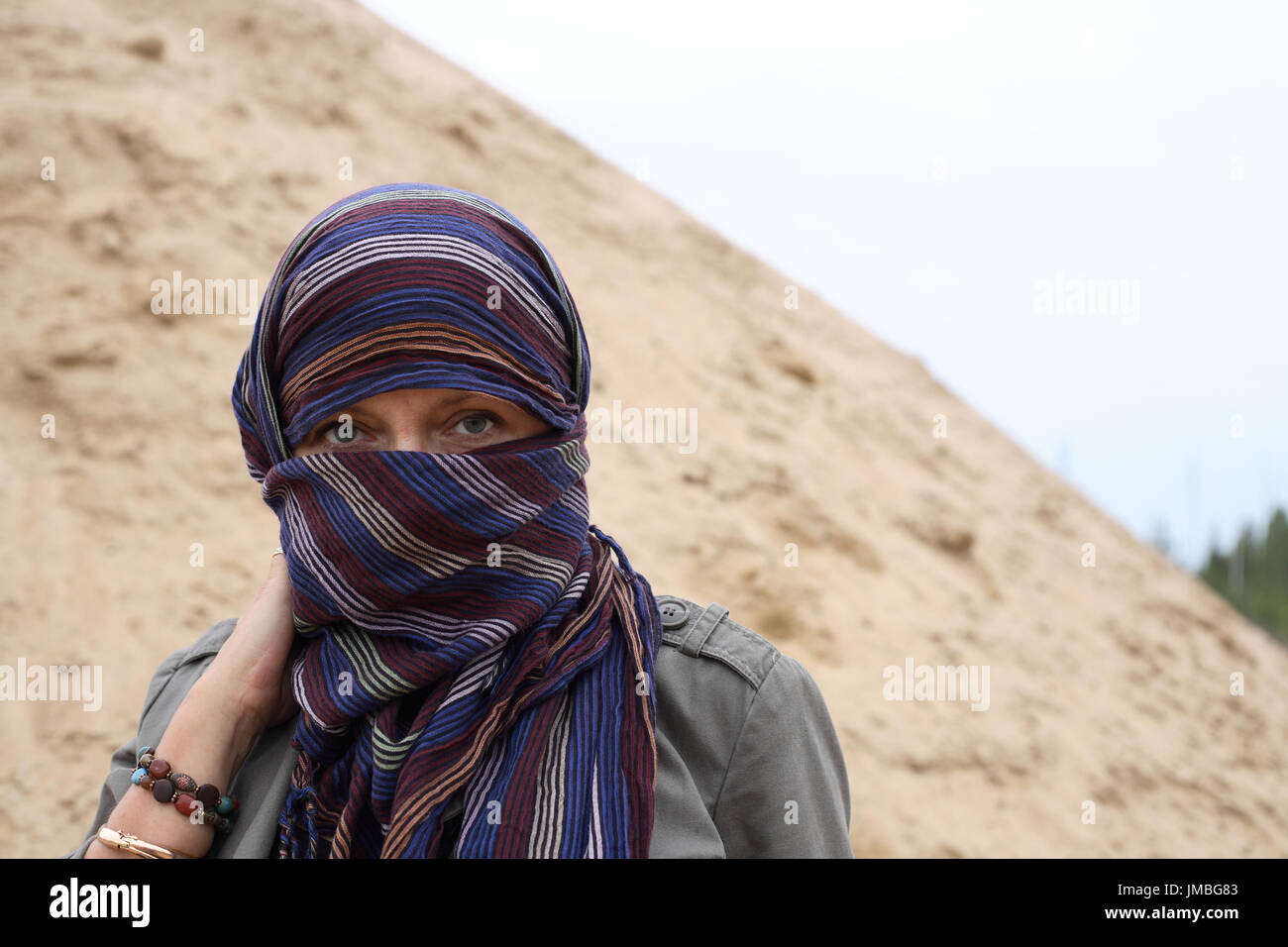 Eastern woman in yashmak over the background with sand and sky - Stock Image