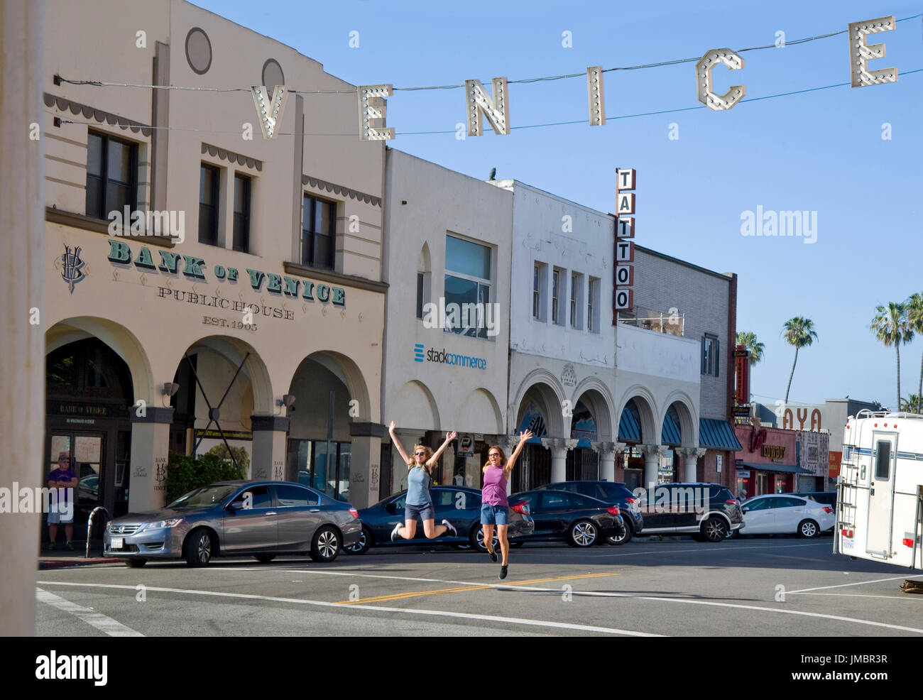 Two young woman posing for a photo jump in the air beneath the Venice Sign in Venice Beach, CA - Stock Image