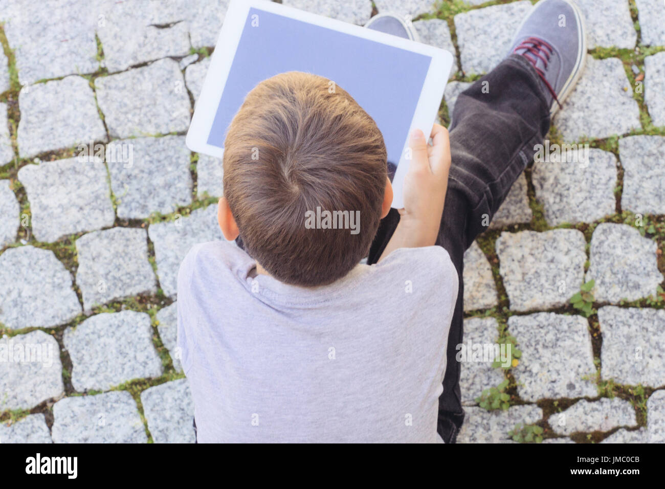 Young boy with tablet computer outdoors - Stock Image