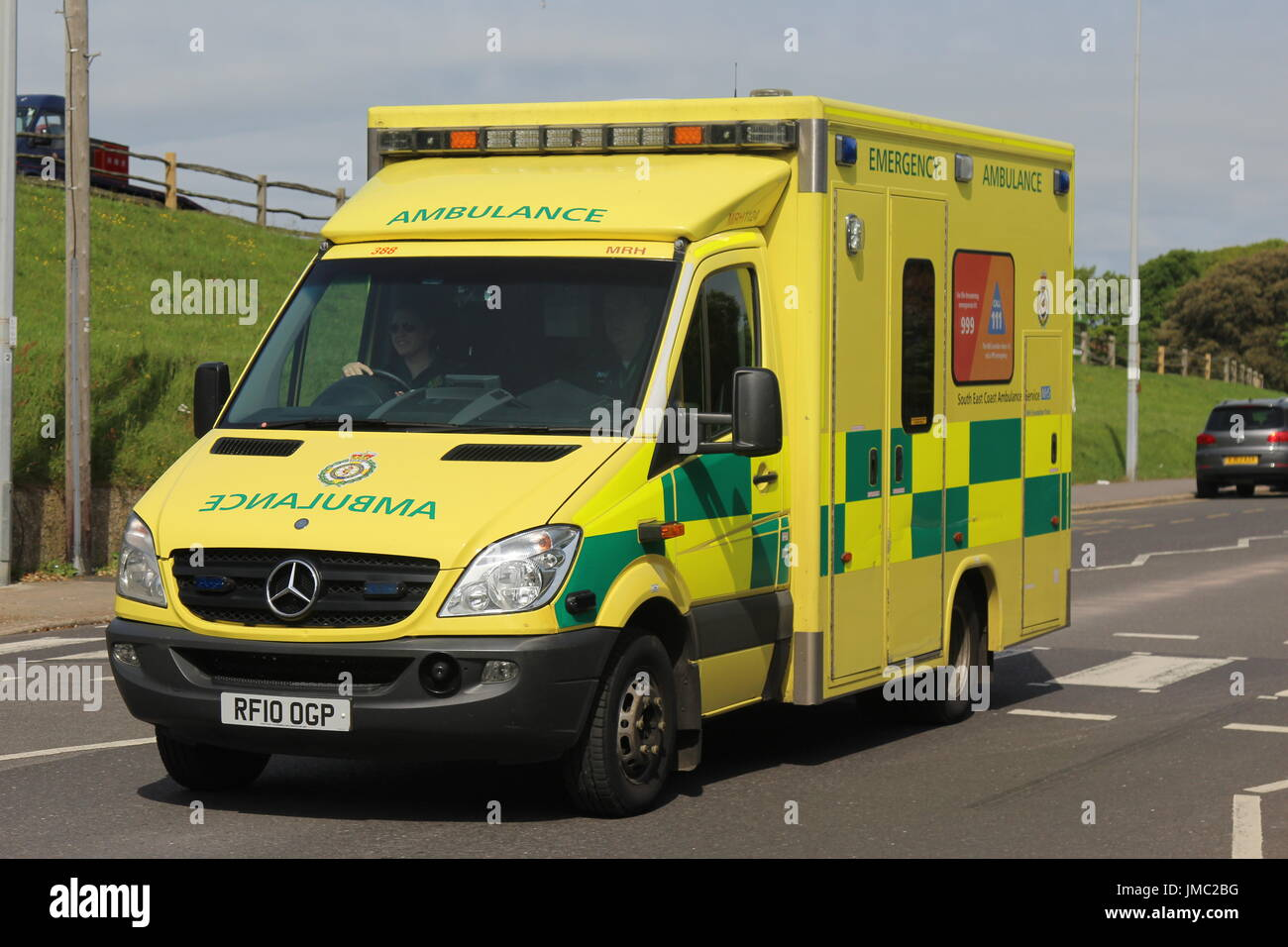 A SUNNY NEARSIDE LANDSCAPE VIEW OF A SOUTH EAST COAST AMBULANCE SERVICE VEHICLE DRIVING ALONG A ROAD - Stock Image