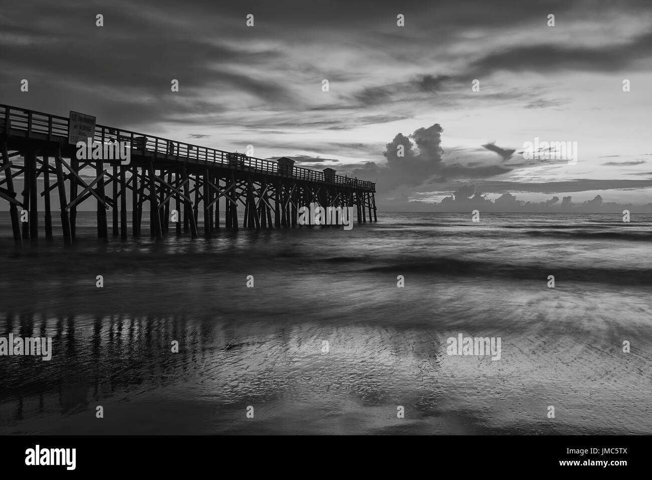 A B&W image of sunrise over the Atlantic Ocean at the pier in Flagler Beach, Florida. - Stock Image