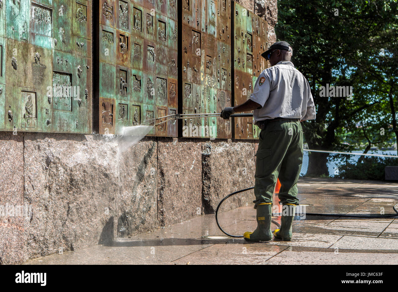 An editorial image of a park employee power washing a wall of a monument in Washington DC. - Stock Image