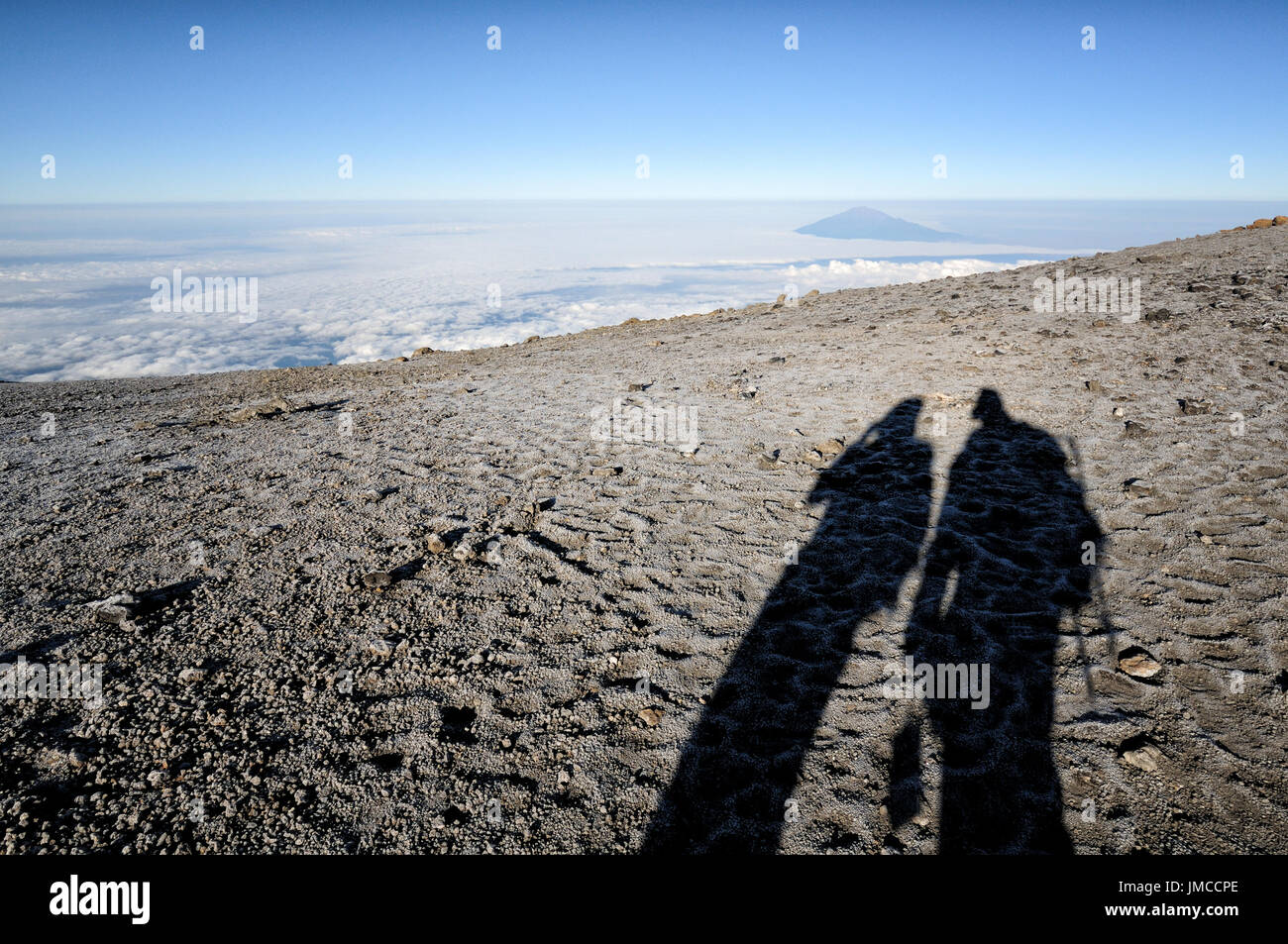 Shadows of trekkers with mount meru in the distance near the summit kilimanjaro national park