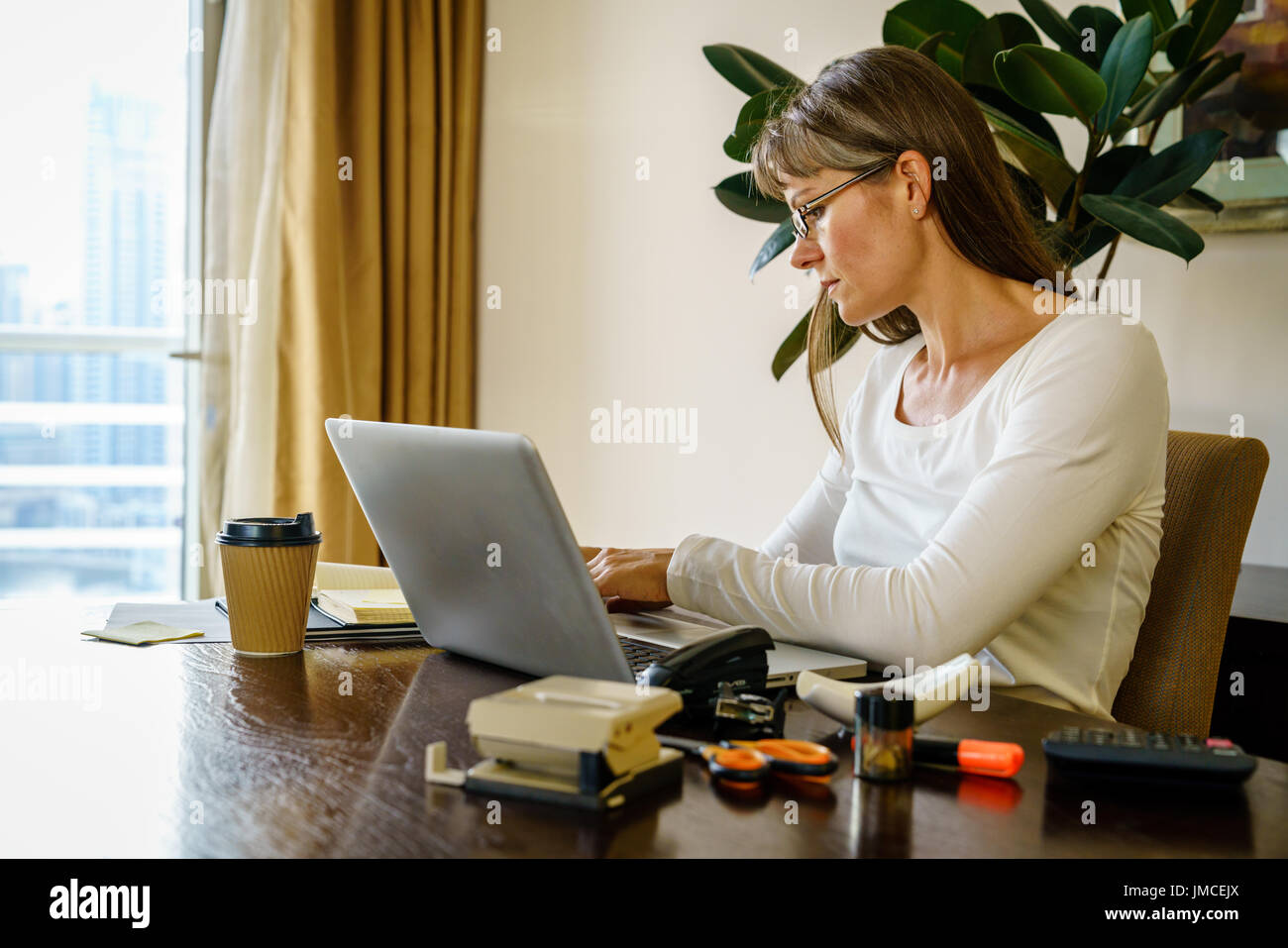 Woman is working in her home office - Stock Image