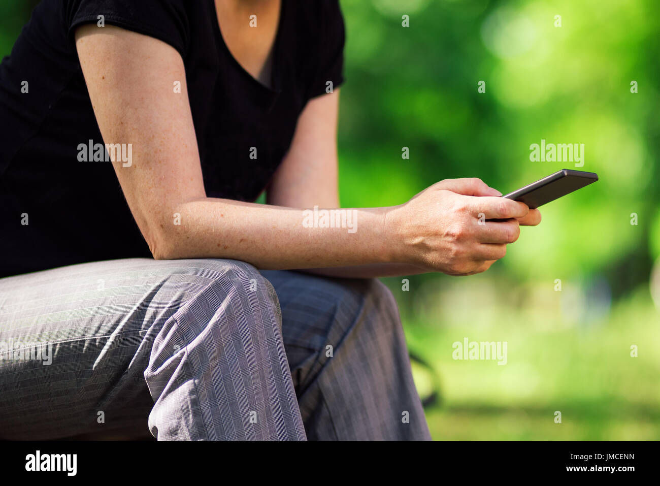 Social network addict using smartphone outdoors in park to share, follow and post to social media - Stock Image