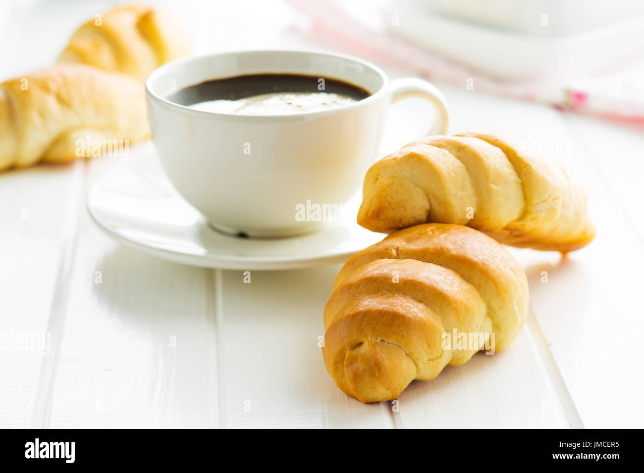 Sweet tasty croissants and coffee cup on white table. - Stock Image