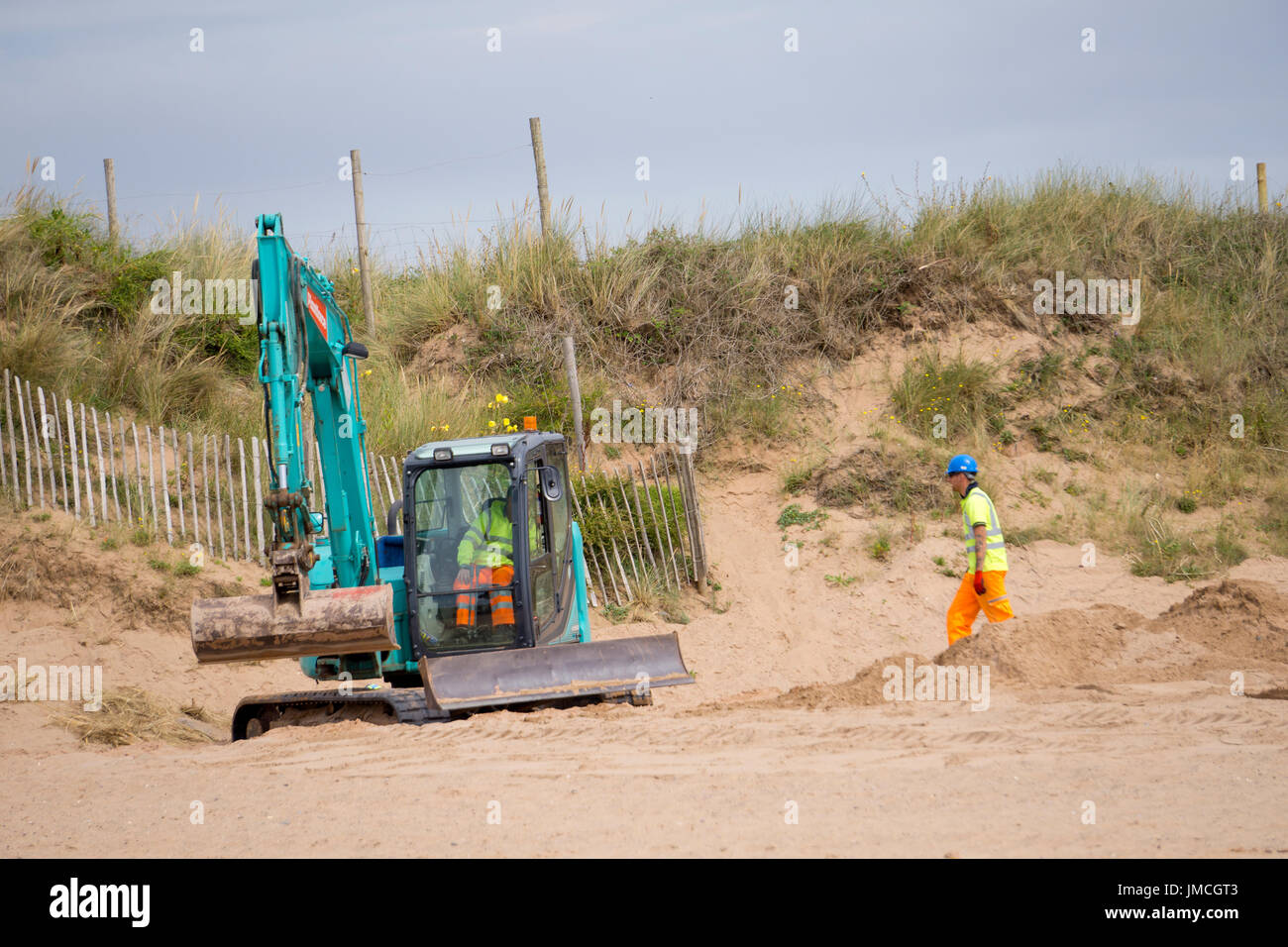 Workers moving sand with diggers and building access to the beach at Dawlish warren, Devon, England, UK - Stock Image