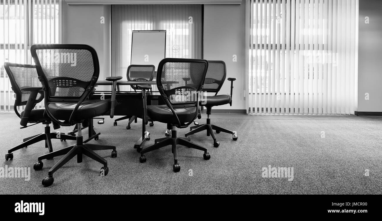 Ergonomic office chairs around a table. Empty conference room. Vertical window blinds. Black and white - Stock Image