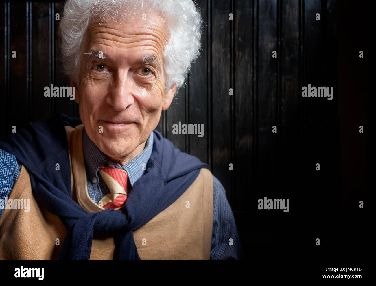 Senior man portrait. Close up, looking at camera. Smiling, well dressed, leaning against dark wall - Stock Image
