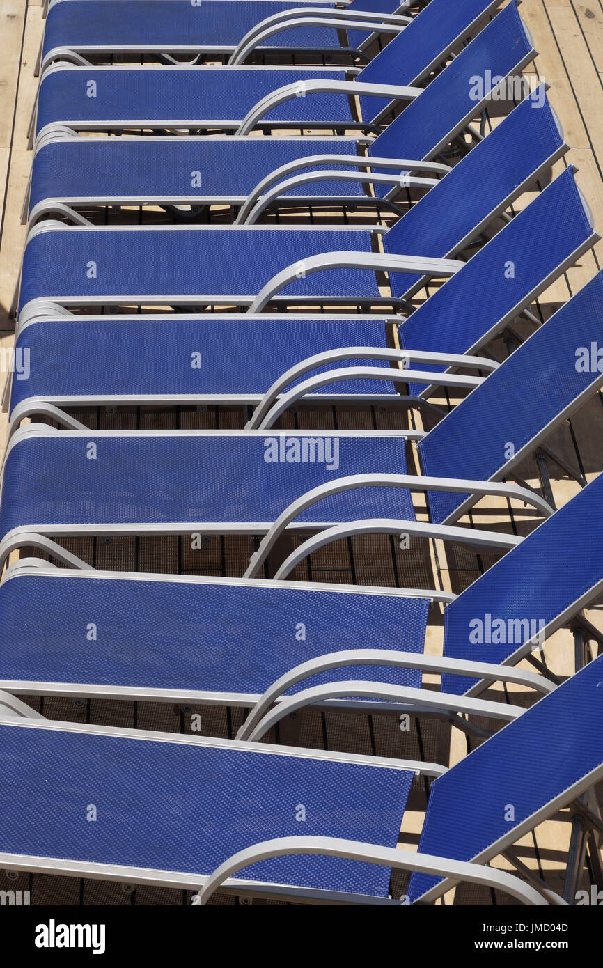 Deckchairs lined up by the pool on a cruise ship - Stock Image