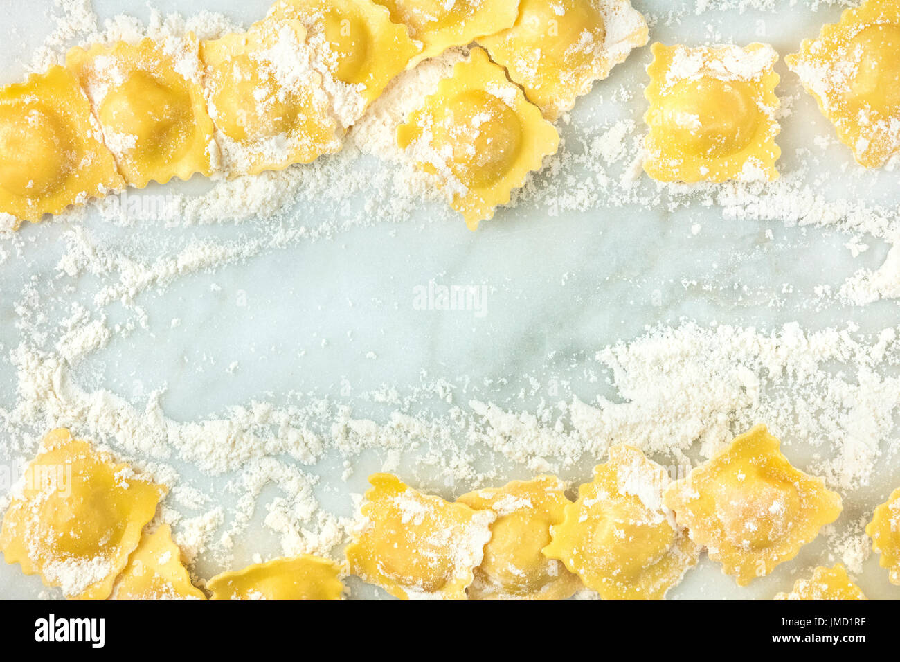 Overhead photo of ravioli with flour and copy space - Stock Image