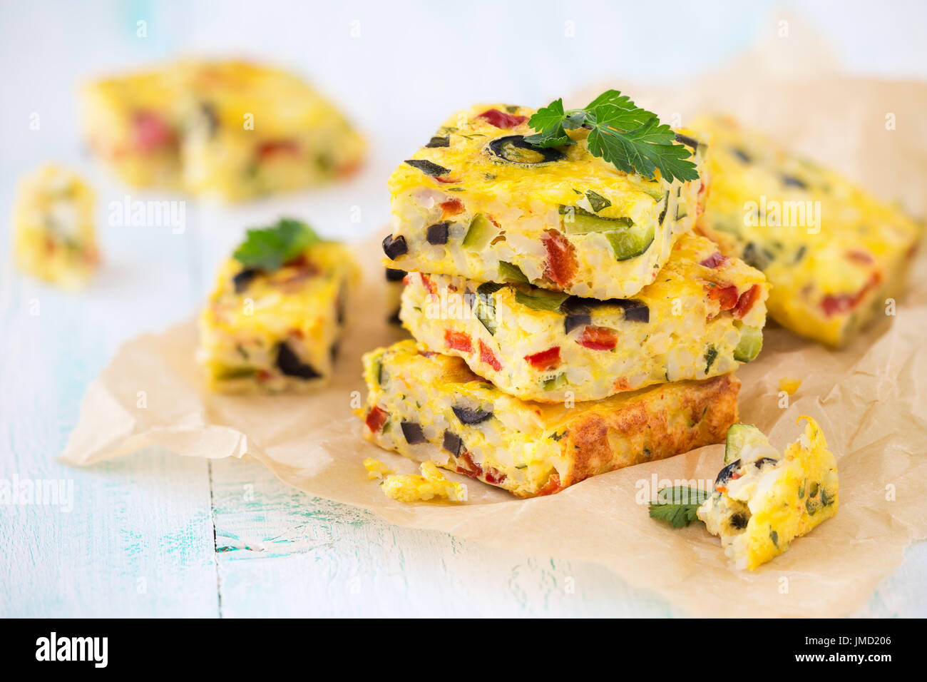 Homemade vegetarian rice frittata with zucchini, bell pepper and olives - Stock Image