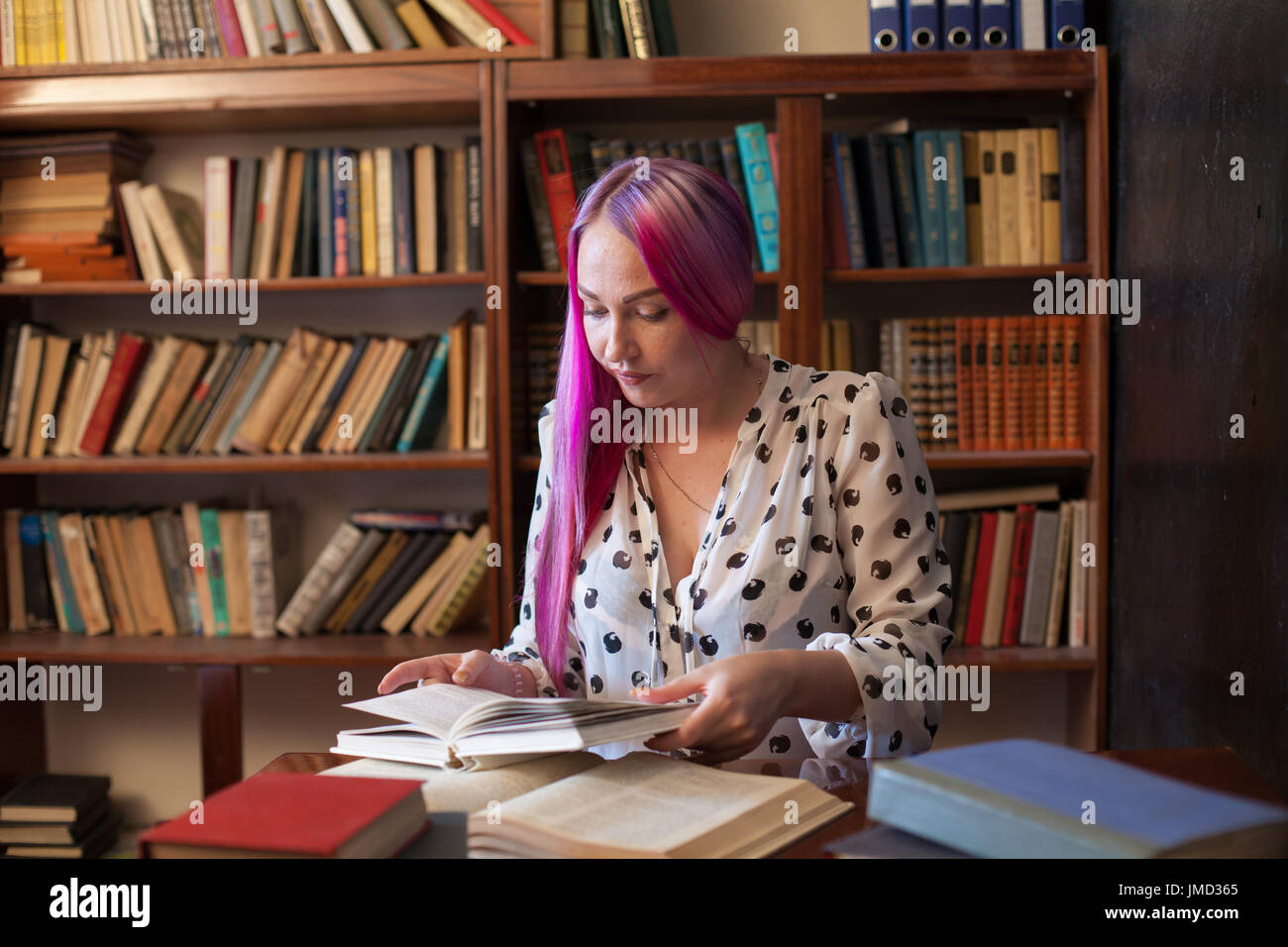 girl reading a book in the library is preparing for exams - Stock Image