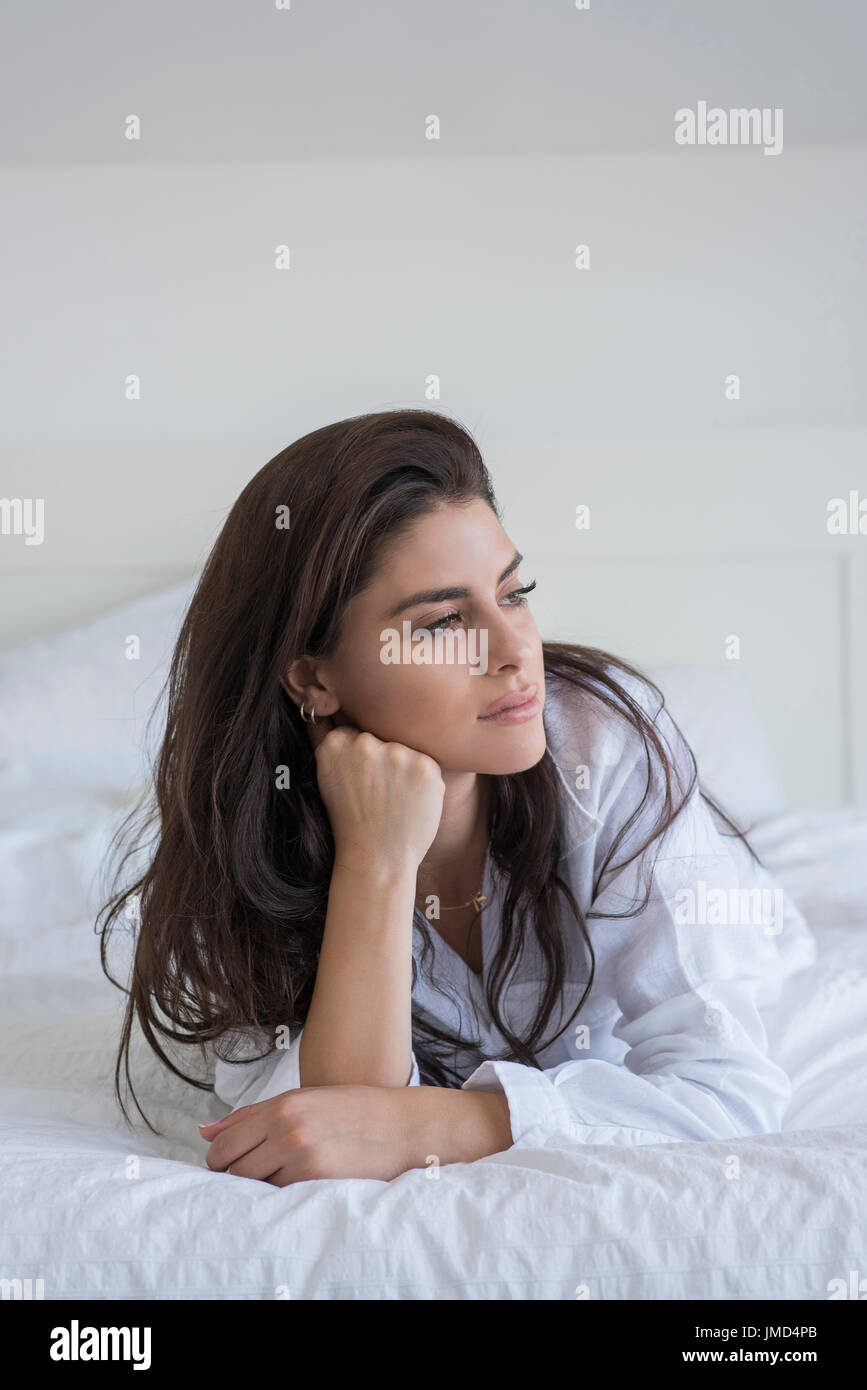 Young woman lying on bed and wearing a white shirt. She is leaning on elbow and looking away. Stock Photo