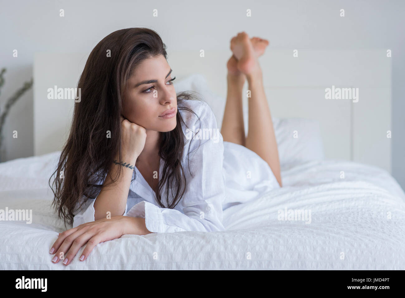 Young woman lying on bed and wearing a white shirt. She is leaning on elbow and looking away. - Stock Image
