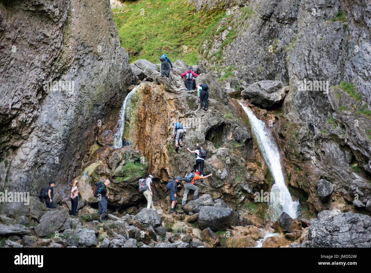 Walkers clamber up the footpath over the waterfalls at Gordale Scar, Malham, Yorkshire Dales National Park, UK - Stock Image