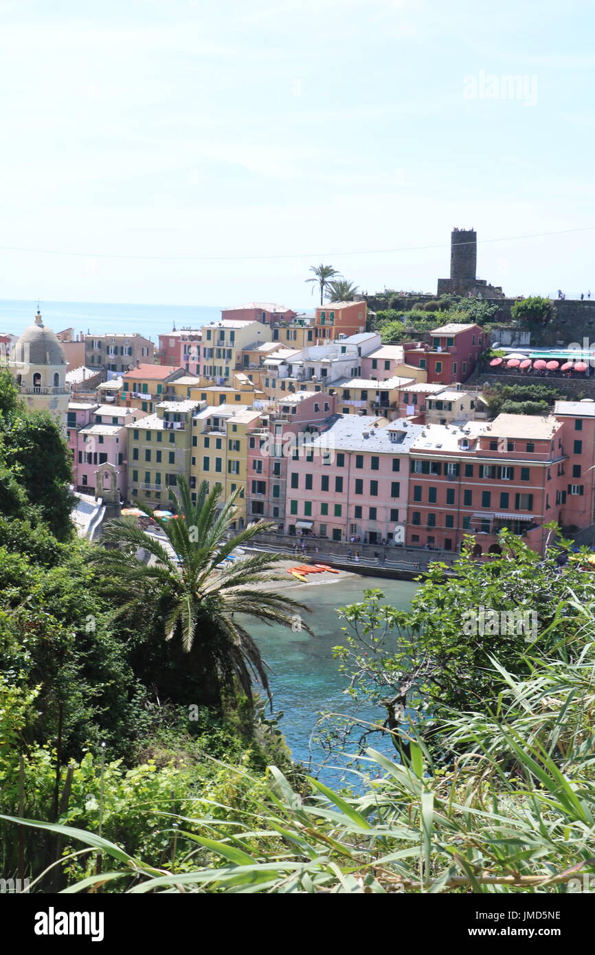 View of one of the five villages with colourful buildings along the shore of the clear blue sea in Cinque Terre, Italy - Stock Image