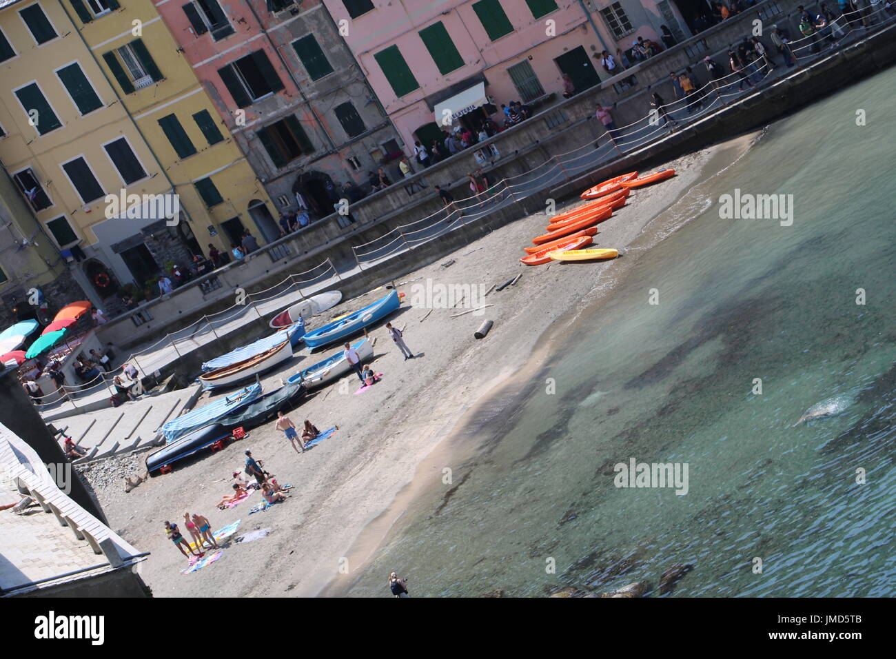 Small beach between colourful buildings where people sunbathe in one of the villages in Cinque Terre, Italy - Stock Image