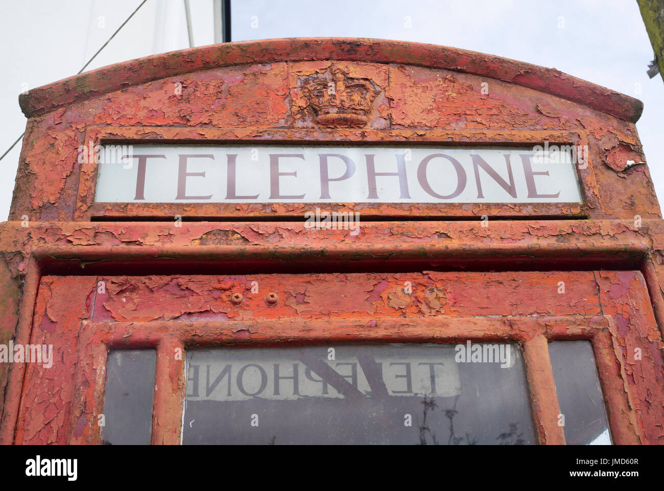Weathered British telephone box kiosk with paint peeling off, Trispen, St Erme, Cornwall England UK. - Stock Image