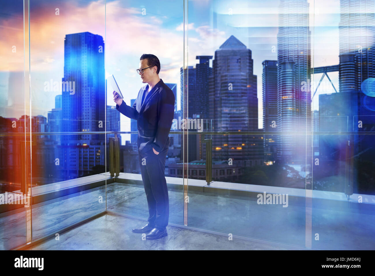 Businessman use digital device stand at modern transparent office with beautiful city skyline , evening scene . - Stock Image