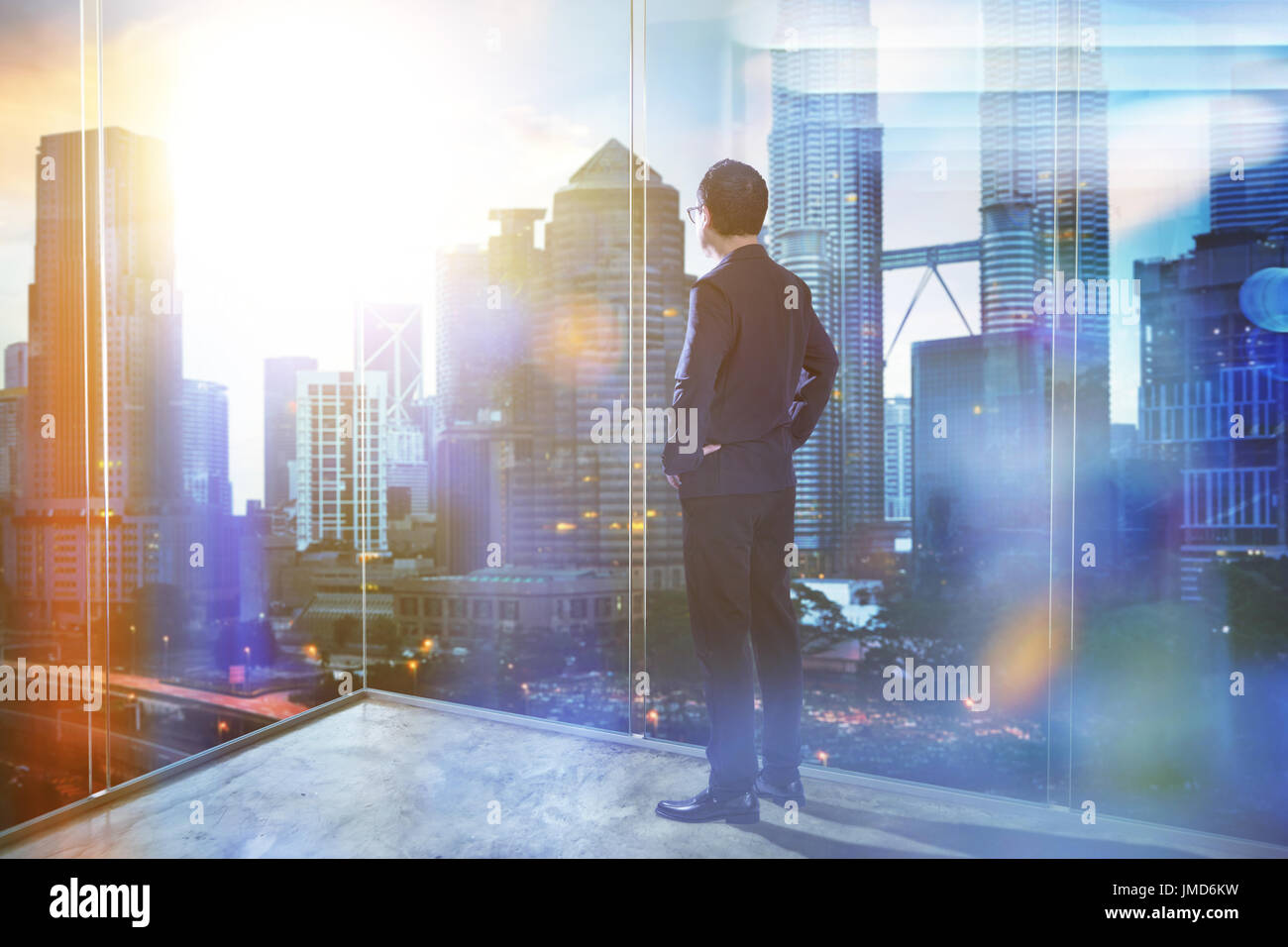 Young businessman looking out the city in the office . morning scene. . - Stock Image