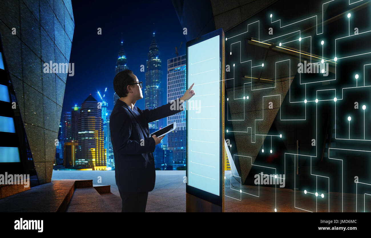 Smart businessman touch the screen to search the information of intelligent communication network of things . Night scene with modern city background  - Stock Image