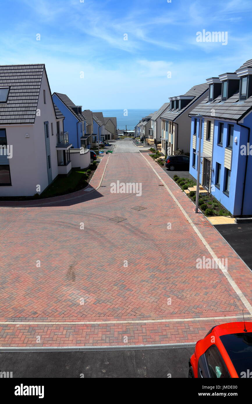 The room with a view, looking out along the street towards the sea with new houses on either side leading downwards to water. Stock Photo