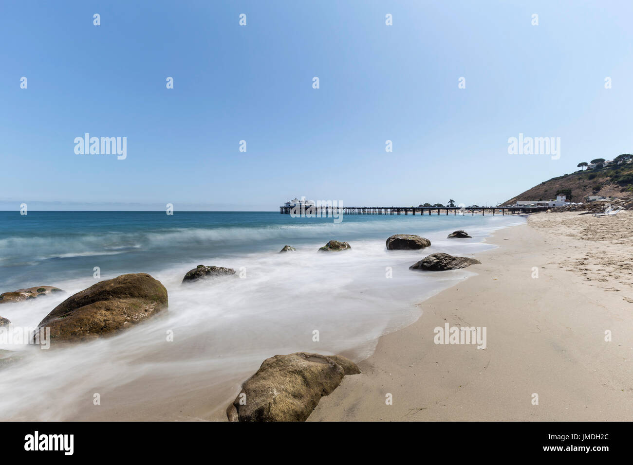 Malibu Pier beach with motion blur surf near Los Angeles in Southern California. - Stock Image