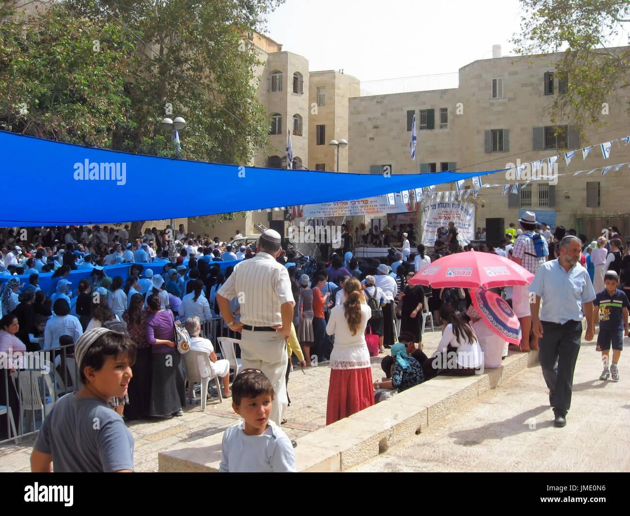 A crowd of Jewish people celebrate Sukkot in the Jerusalem Old City Jewish Quarter. - Stock Image