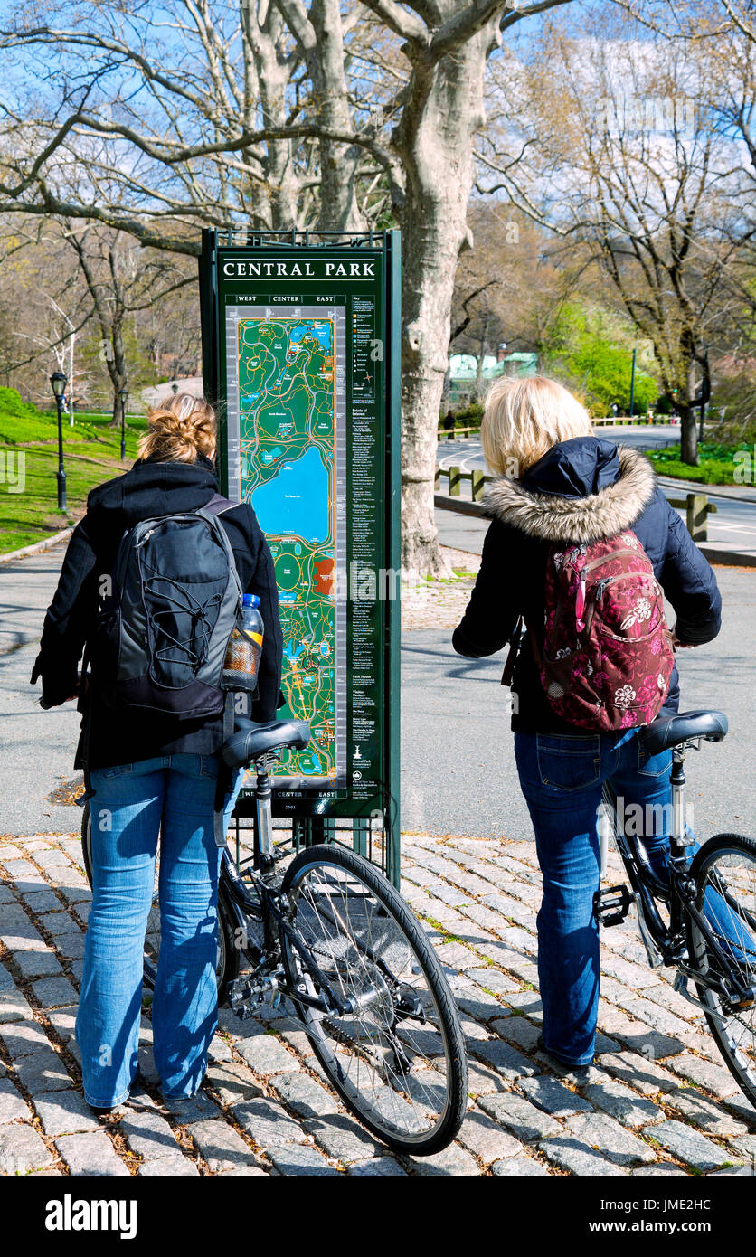 Two women on bikes in Central Park, New York City, stop to ... on central park path map, central park interactive map, central park lights, central park road map, central park plan, central park visitors map, central park walking map, central park trail map, central park statues, central park new york, central park at night, central park field map, central park jogging map, central park skating, central park mall, central park guide, central park bicycle, central park in the snow, central park tree map, central park biking,
