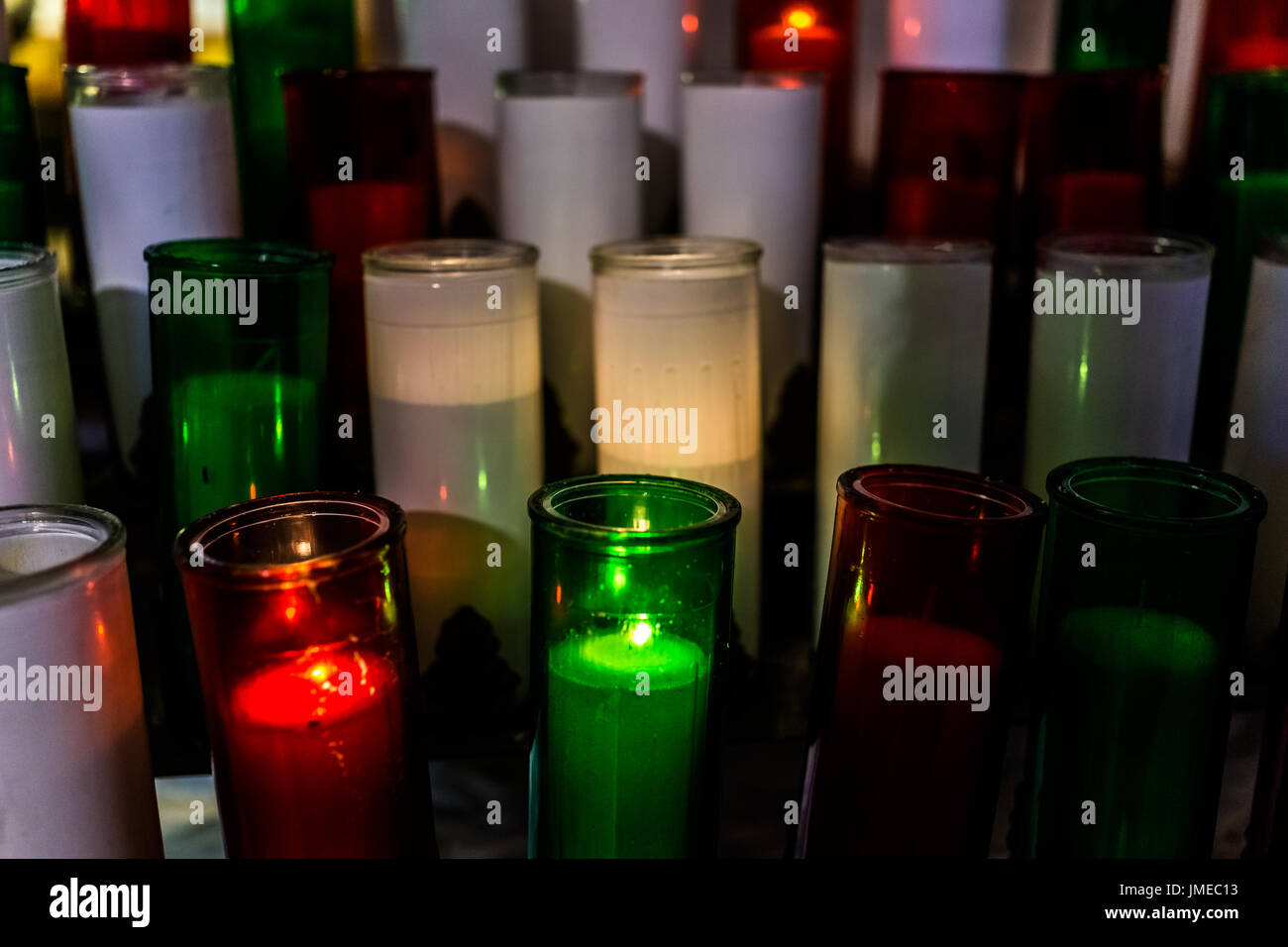 Macro closeup of red, green and white candles with yellow flame in church - Stock Image