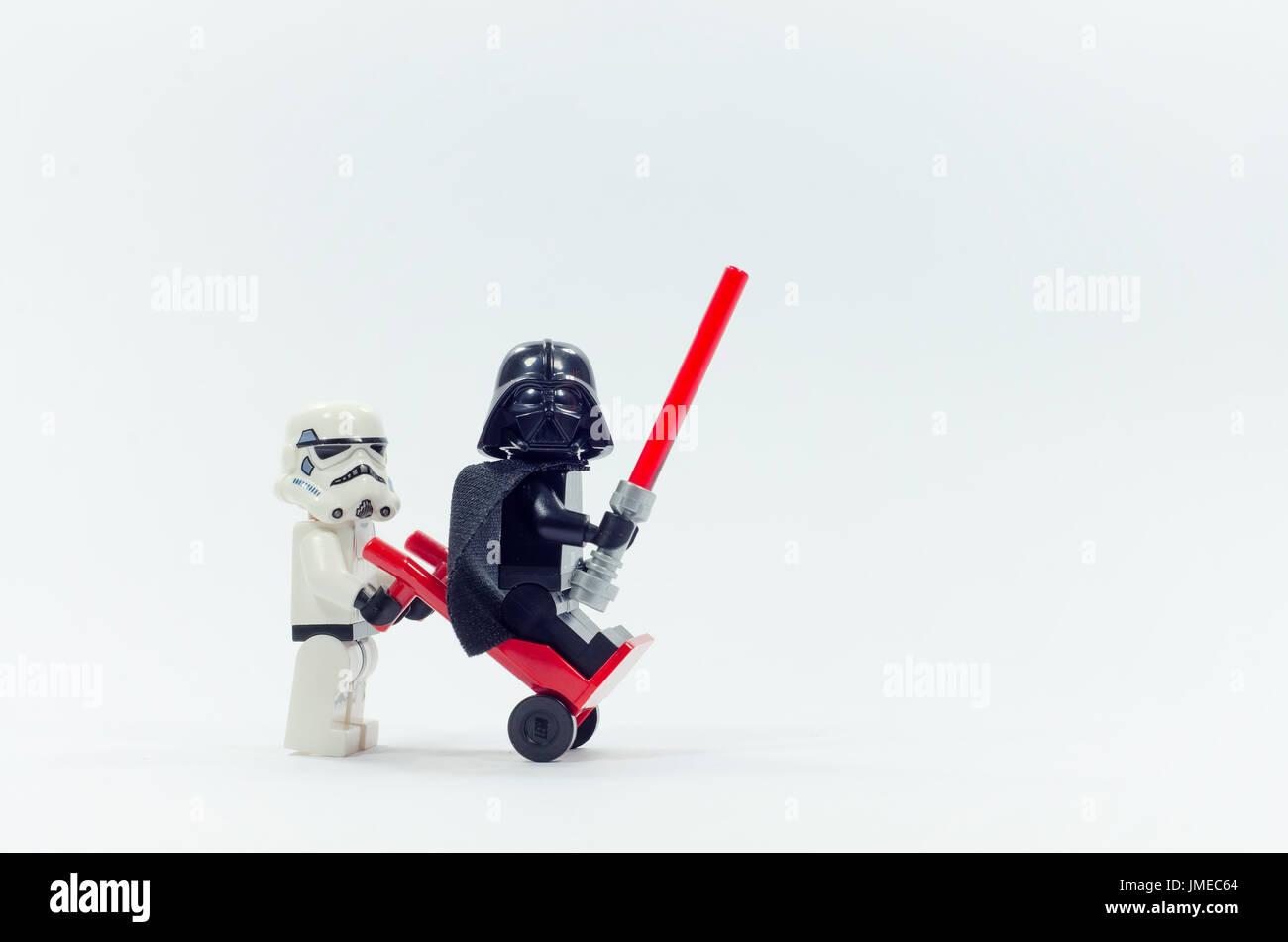 lego darth vader sitting on trolley while storm trooper push it. isolated on white background. - Stock Image