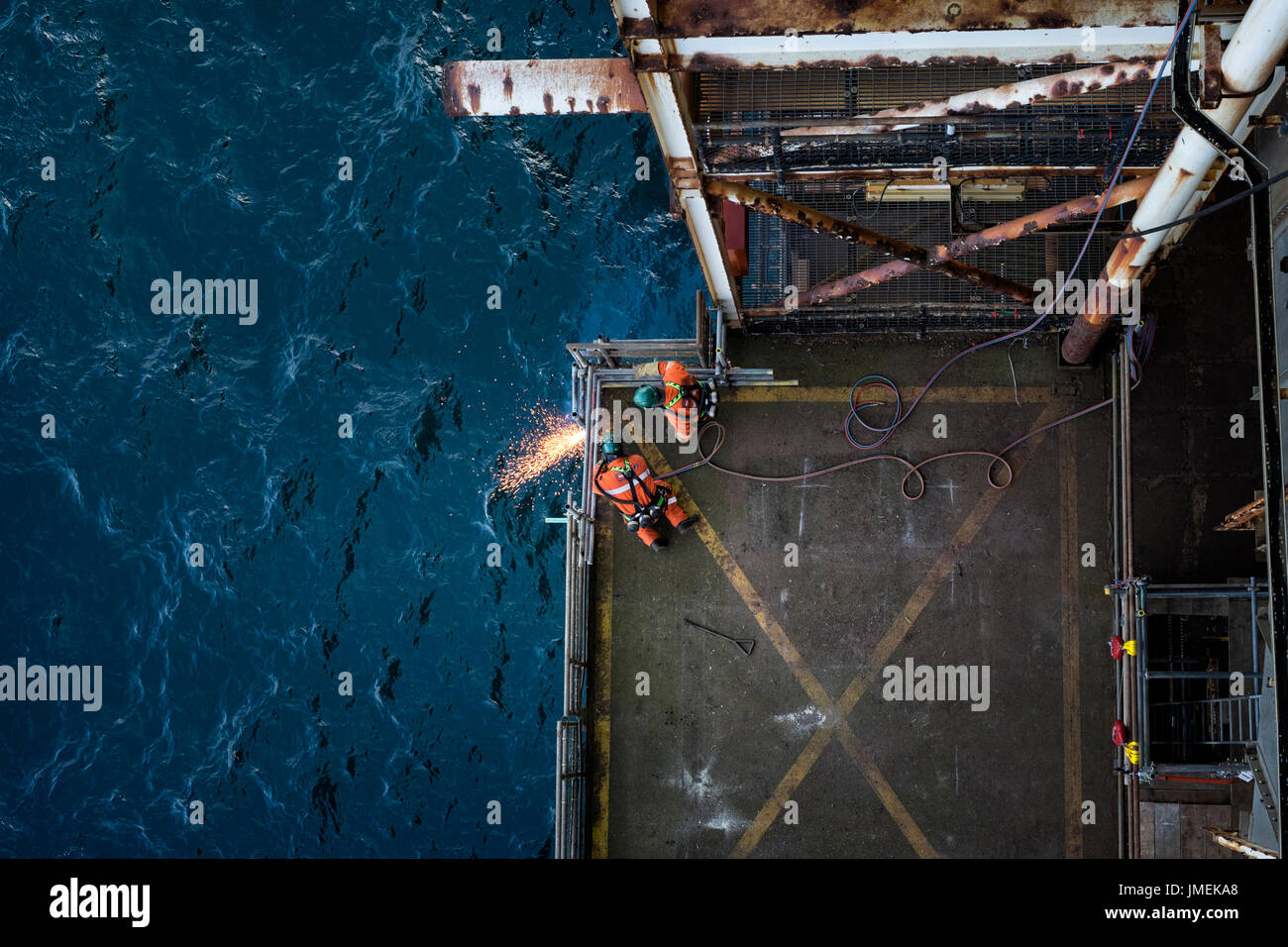 Image of industrial workers, using oxy acetylene cutting torches on the decommissioning of a north sea oil rig. credit: LEE RAMSDEN / ALAMY - Stock Image
