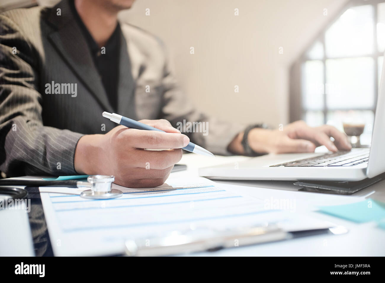 Insurance agent holding pen medical insurance, the policy and explain insurance policy to customer. life insurance concept. - Stock Image