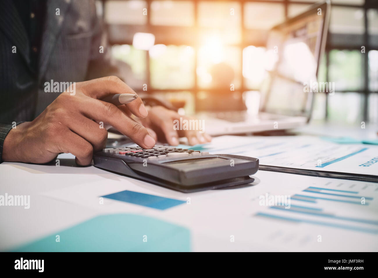 Insurance agent using calculator for medical insurance, the policy and explain insurance policy to customer. life insurance concept. - Stock Image