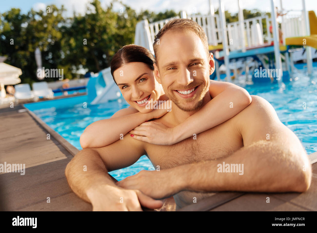 Nice time together. Happy loving young couple standing in the swimming pool and smiling at the camera while the woman hugging her boyfriend from behin - Stock Image