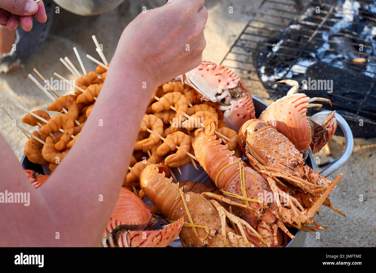 Vietnamese seefood grilled on fire at directly at the beach in Nha Trang, Vietnam. - Stock Image