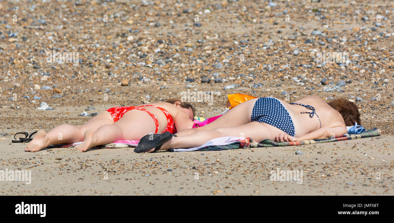 Sunbathing. Pair of young female sunbathers on a shingle beach in Summer in the UK. - Stock Image