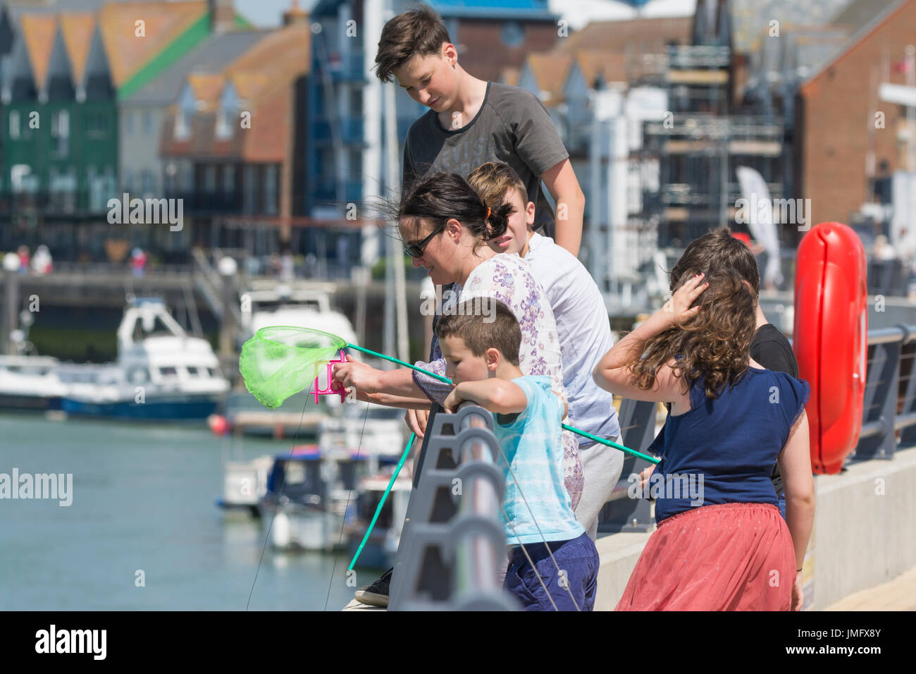 Crab fishing. Young people fishing for crabs by the river in Littlehampton, West Sussex, England, UK. - Stock Image