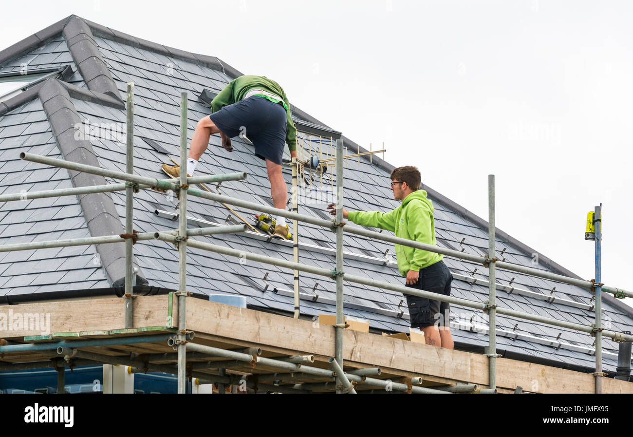 Workmen repairing roof and tiles on the roof of a house. - Stock Image