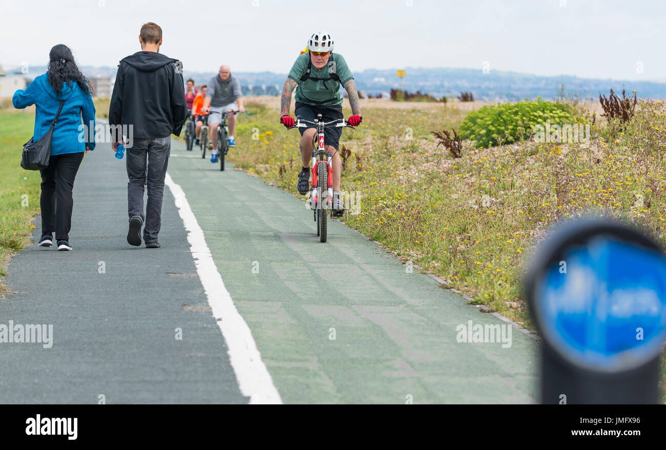 Pavement with pedestrian lane and cycle lane (cycle track) in the UK. People walking. Cyclists in cycle lane. - Stock Image