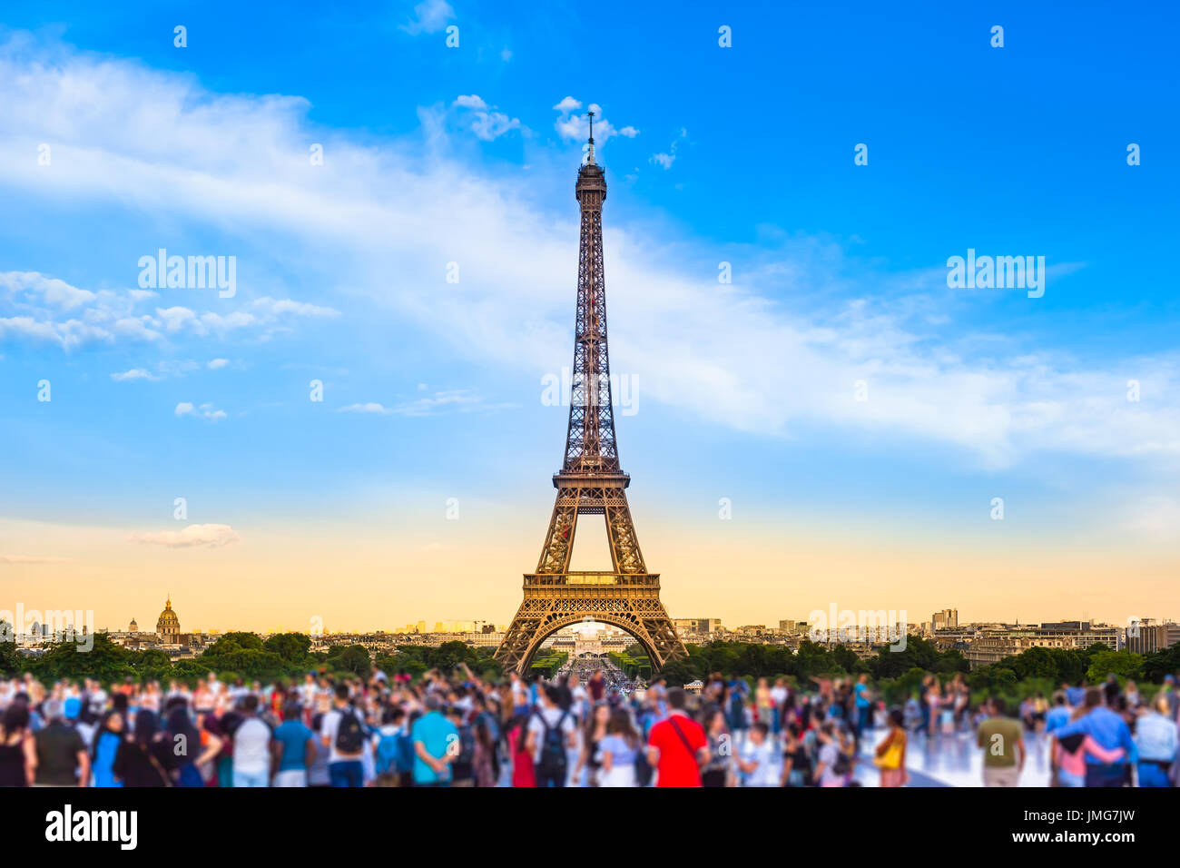 Colorful large group of unrecognizable people blurred in front of Paris Eiffel Tower at evening light (copy space) - Stock Image