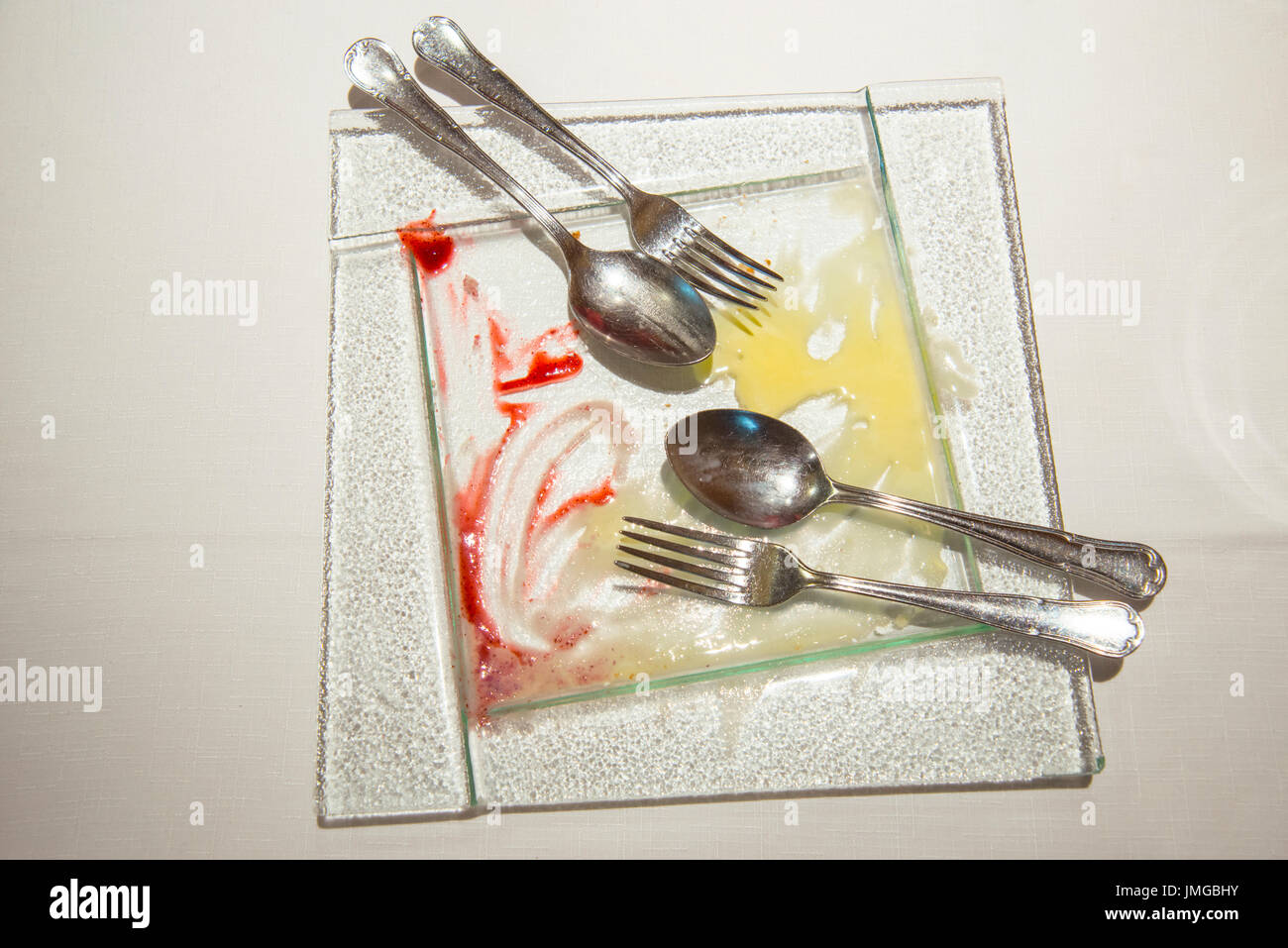 Empty dessert dish with two spoons and two forks. - Stock Image